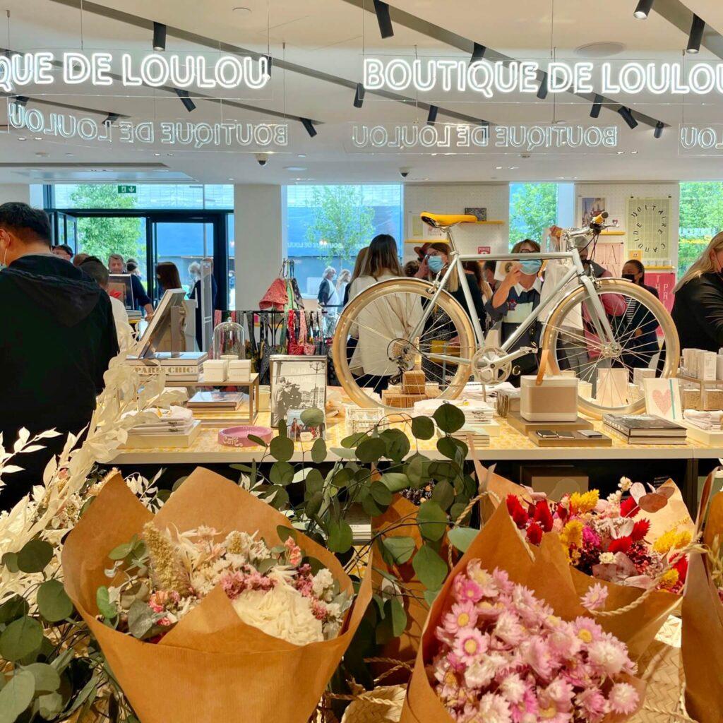 Esta imagen ilustra la boutique de Loulou en la Samaritaine, se ven unas flores en primer plano, y unos estantes con una bicicleta encima, libros y personas viendo los productos propuestos por La Samaritaine en Paris