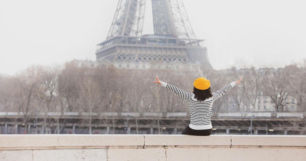 mujer mirando a la torre eiffel con los brazos abiertos y vestida con una marinera y una boina francesa